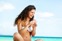 Portrait of a happy young woman posing while on the beach. Portrait of a happy beautiful young woman posing while on the beach Royalty Free Stock Photo