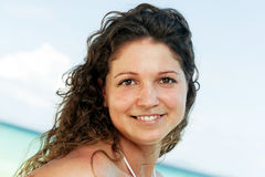 Portrait of a happy young woman posing while on the beach. Portrait of a happy beautiful young woman posing while on the beach Royalty Free Stock Photography