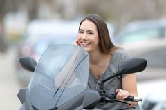 Biker posing looking at camera on a motorbike. Portrait of a happy biker posing looking at camera on a motorbike on the street Royalty Free Stock Photos