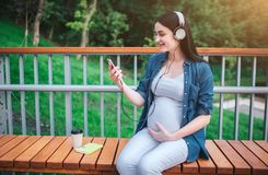 Portrait of a happy black hair and proud pregnant woman in a city in the background. She is sitting on a city bench stock photos