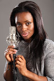 Portrait happy black woman singer in music studio. Happy beautiful young black woman singer in the recording studio taking a relaxing break. She is standing next royalty free stock image