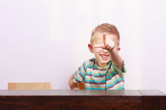 Portrait of happy blond boy child kid pointing at you at the table Royalty Free Stock Images