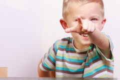 Portrait of happy blond boy child kid pointing at you at the table Royalty Free Stock Photos