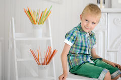 Portrait of happy blond boy child sitting on chair royalty free stock photos
