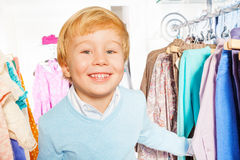 Portrait of happy blond boy standing near hangers Stock Photography