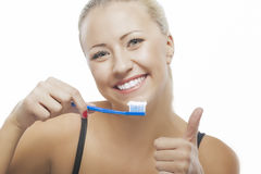 Portrait of Happy Blond Caucasian Woman Cleaning Her Teeth with Royalty Free Stock Image