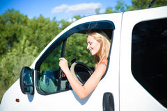 Portrait of happy blond woman driving white car Royalty Free Stock Photography