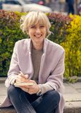 Portrait of a happy woman thinking. Portrait of a happy blond woman thinking and going to write Royalty Free Stock Images