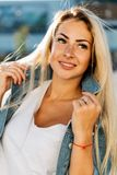 Portrait of happy blonde woman on blurred background in city royalty free stock photography