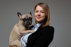 Portrait of a happy blonde woman breeder holds her cute pug. Isolated on gray background. stock image