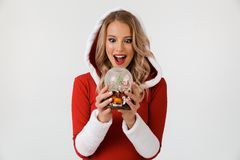 Portrait of a happy blonde woman. Dressed in red New Year costume standing over white background, holding snowball stock images