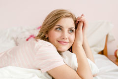 Portrait of happy blue eyes young blond lady having fun relaxing in bed with floral pillow in hand and happy smiling Royalty Free Stock Photos