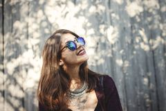 Portrait of happy boho girl in cool outfit and sunglasses smiling in sunlight. Stylish hipster girl posing in sunny street on. Background of wooden wall. Space royalty free stock image