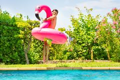 Happy boy with swim toy jumping in swimming pool. Portrait of happy boy with big inflatable flamingo jumping in the outdoor swimming pool stock photography