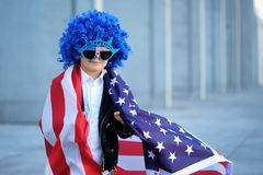 A portrait of happy boy in blue wig holding american flag. A five years old happy boy wearing a blue wig and glasses in the shape of a statue of liberty on grey Royalty Free Stock Photos