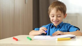Portrait of a happy boy caucasian appearance, who sits at the table and draws felt pen in the album. The child looks at