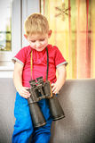Portrait of happy boy child kid playing with binoculars. At home. Stock Image