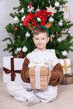 Portrait of happy boy in deer costume with gift boxes and Christ. Portrait of happy boy in deer costume with gift boxes and decorated  tree Stock Images