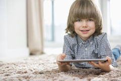 Portrait of happy boy with digital tablet lying on rug at home Stock Photography