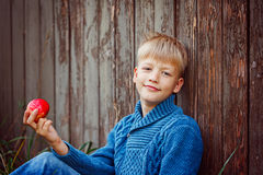 Portrait of happy boy eating an apple outside in the garden Stock Photo