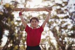 Portrait happy boy exercising with log during obstacle course stock photo