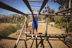 Portrait of happy boy exercising on monkey bar during obstacle course. In boot camp Stock Photo