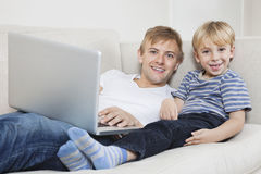 Portrait of happy boy with father using laptop on sofa Stock Photography