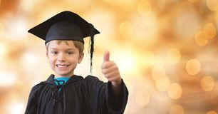 Portrait of happy boy in graduation gown and mortar board showing thumb up over bokeh Royalty Free Stock Photo
