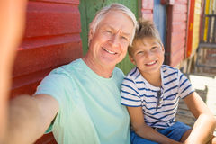 Portrait of happy boy with grandfather sitting by wall. At beach Stock Image