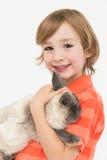 Portrait of happy boy holding fluffy rabbit Stock Photos