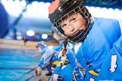 Portrait of happy boy in ice hockey uniform. Close-up portrait of boy wearing ice hockey uniform smiling and looking camera royalty free stock images