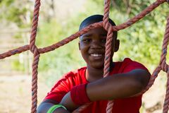 Portrait of happy boy leaning on net during obstacle course. In the boot camp royalty free stock photography