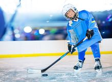 Happy little hockey player passing the puck. Portrait of happy boy, little hockey player, standing on ice rink and passing the puck royalty free stock photos