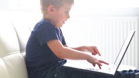 Portrait of happy boy playing with computer. Attractive kid with a laptop at home. Entertainment technology, futuristic. Gadgets, internet and generation Z stock footage