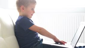 Portrait of happy boy playing with computer. Attractive kid with a laptop at home. Entertainment technology, futuristic. Gadgets, internet and generation Z stock video footage