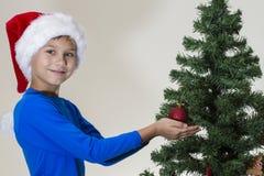 Portrait of happy boy in Santa cap decorating Christmas tree Royalty Free Stock Photos