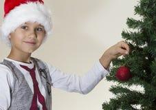 Portrait of happy boy in Santa cap decorating Christmas tree Stock Images