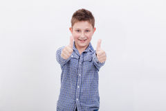 Portrait of happy boy showing thumbs up gesture. Over white background Stock Image