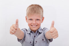 Portrait of happy boy showing thumbs up gesture. Over white background Stock Photography
