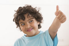 Portrait of happy boy showing thumbs up gesture. Wearing blue t-shirt Royalty Free Stock Photos