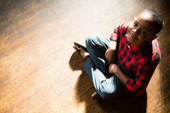 Portrait of happy boy sitting on wooden floor Royalty Free Stock Images