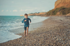 Portrait of happy boy standing alone at beach.  Stock Photos