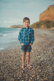 Portrait of happy boy standing alone at beach.  Stock Images