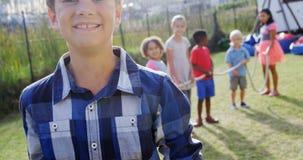 Portrait of happy boy standing in backyard 4k. Portrait of happy boy standing in backyard while friends standing in background 4k stock video footage