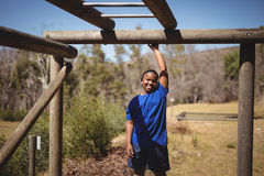 Portrait of happy boy standing on monkey bar during obstacle course Stock Images