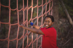 Portrait of happy boy standing near net during obstacle course stock images