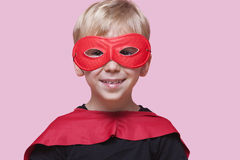 Portrait of a happy boy in superhero costume over pink background Royalty Free Stock Photo