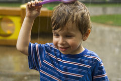 The portrait of happy boy under pouring water Royalty Free Stock Photos