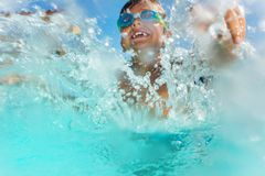 Happy boy having fun splashing water in the pool Stock Photo
