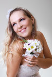 Beautiful young woman in a white dress with a bouquet of flowers Royalty Free Stock Images